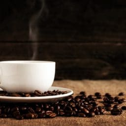 A cup of coffee surrounded by coffee beans